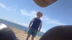 Little boy staring at women on beach