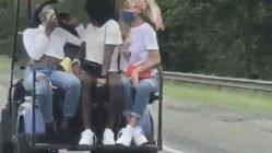 Girls drive golf cart down highway