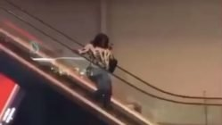 Woman tries to walk down escalator