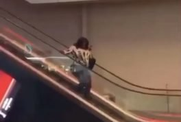 Woman tries to walk down escalator
