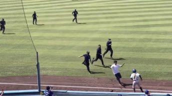 Fan runs through Dogers baseball field during a game