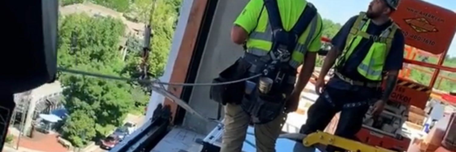 Construction workers screw up window install
