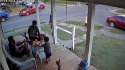 Men take off running from a loose dog while sitting on a porch.